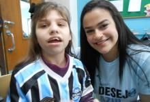 Amanda tem 14 anos e faz tratamento na Kinder. A menina está nesta instituição há cinco anos onde já apresentou vários progressos. Um dos desejos dela era ganhar uma camiseta oficial do Grêmio o que foi possível com a colaboração da voluntária Laila Tubasi.